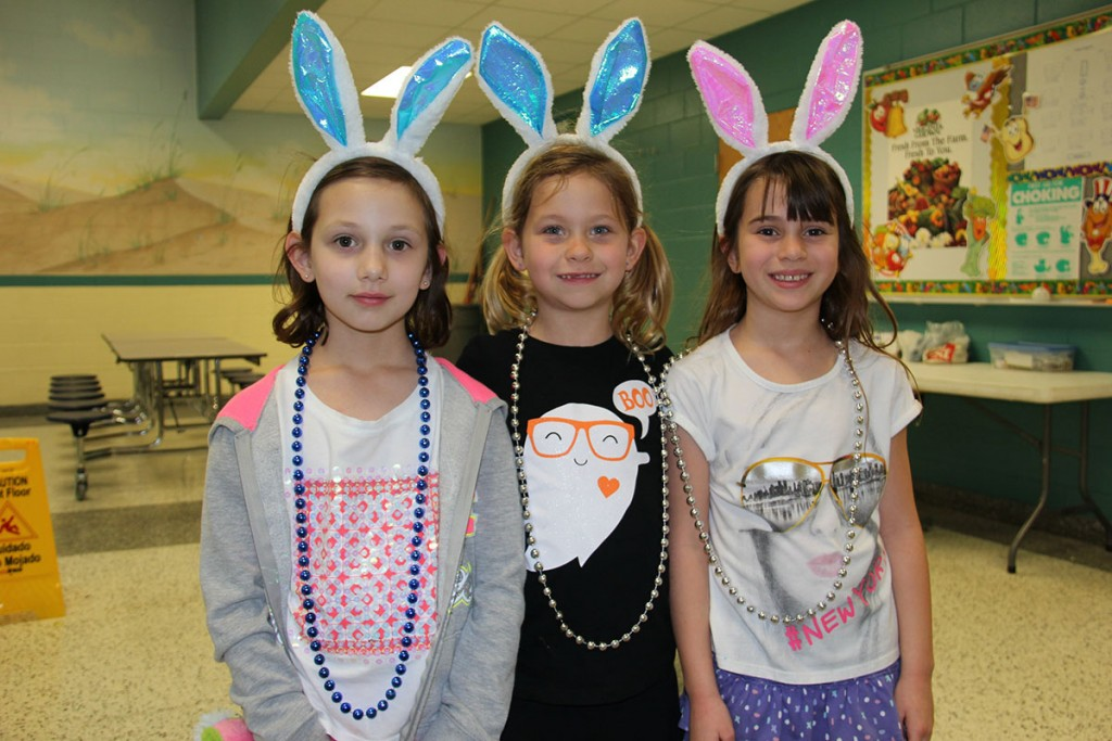 Image of 3 Cooke Elementary students wearing beads with blue beads in the middle and silver beads next to each other