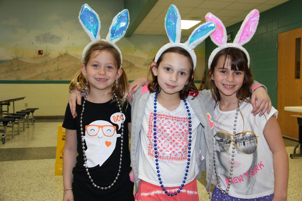 Image of 3 Cooke Elementary students wearing beads with blue beads in the middle and silver beads on either side