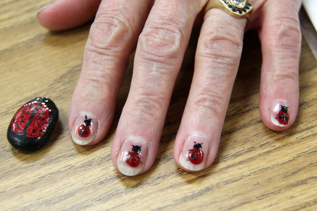 Landstown Elementary volunteer Ruth Hargrave showing hear ladybug art on her fingernails and a rock